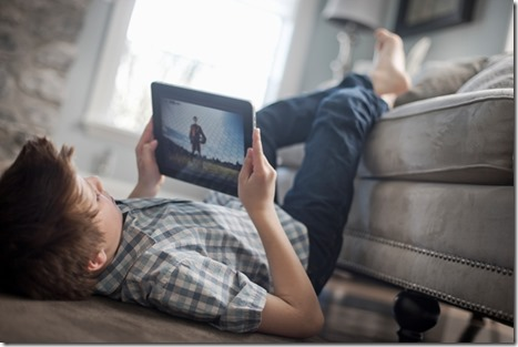 A boy lying on his front on the floor, looking at a digital tablet.