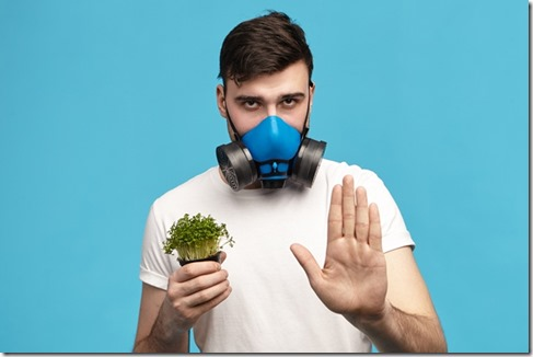 Serious young brunette male in white t-shirt holding micro greens in one hand and making stop gesture with other wearing gas mask, going to spray pesticides to protect plants. Ecology and environment